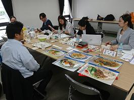 料理の写真などがあるテーブルで向かい合って話をする人々