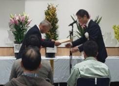 第37回徳島県花き展示品評会で受賞した人が賞状を受け取っている写真です。