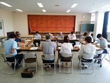 会議室で座って会議をする人々
