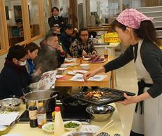 なると金時を料理する女性とその様子を見ている人々