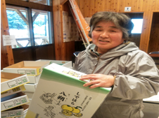 八朔生産者、山口さんが八朔の箱をもって笑っている写真です。